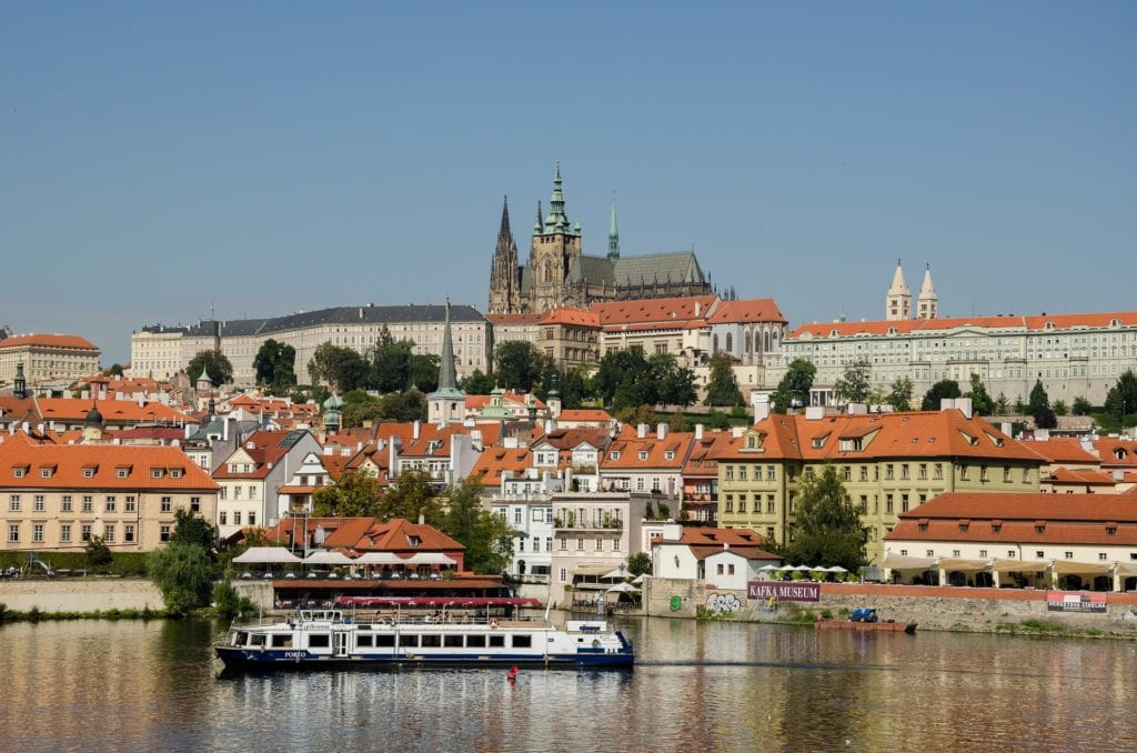 View of Prague from the river with red roofs and a cruise boat.