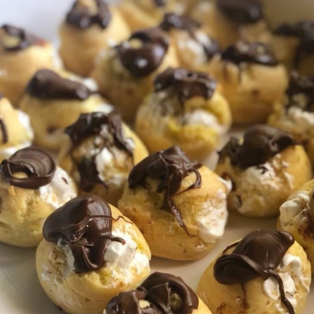 Close-up of many profiteroles topped with a chocolate sauce, small pastry balls that are a traditional French dessert.