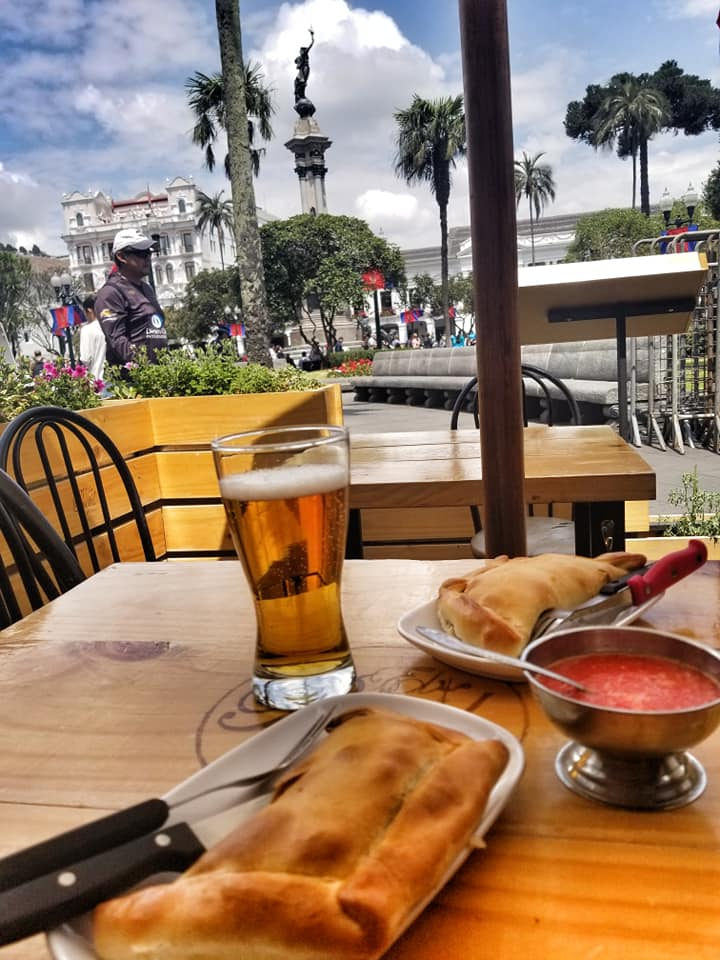 Table at outdoor restaurant with two large empanadas outside Plaza de la Independencia, Quito, Ecuador