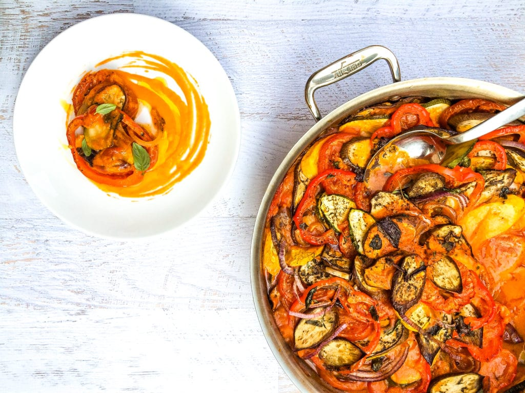 Pot of ratatouille next to a white plate of the traditional French vegetable dish.