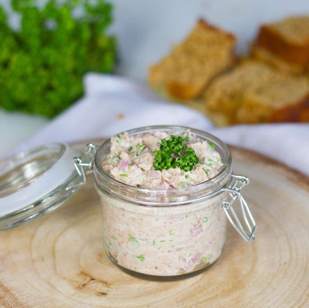 Small glass jar of salmon rillettes topped with chopped chives and some grilled bread in the background.