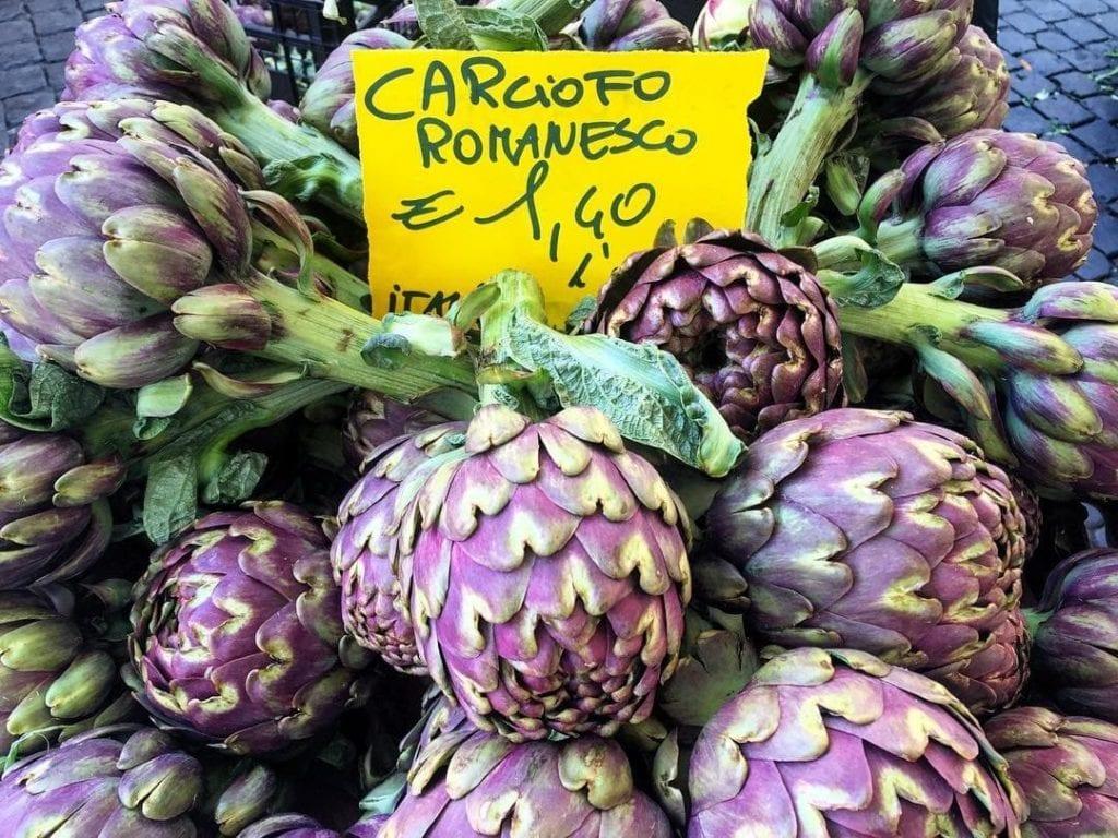 Close-up of Roman artichokes in shades of purple and green with a yellow sign 'Carciofo Romanesco' at Campo di Fiori.