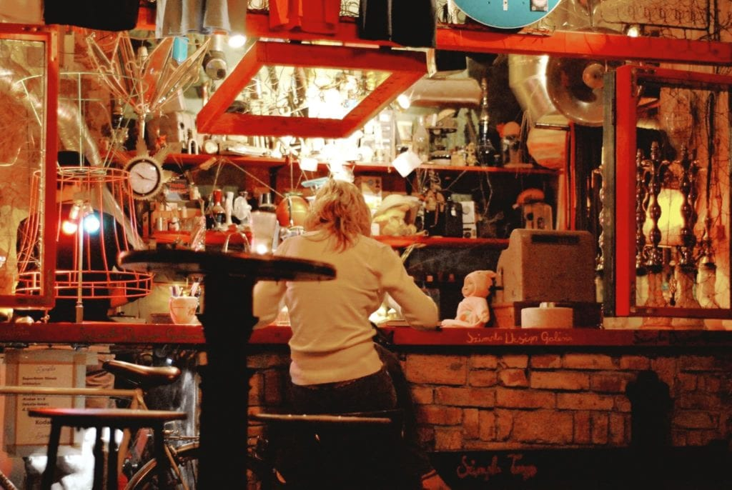 Red, warmly lit interior of one of Budapest's famed ruin bars with a blonde woman ordering a drink at the bar counter.