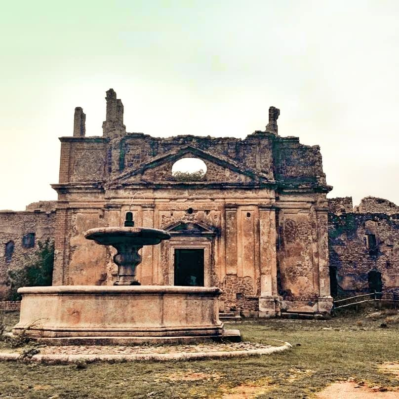 Ancient ruins in Monterano Antica with a broken fountain in front of the old building.