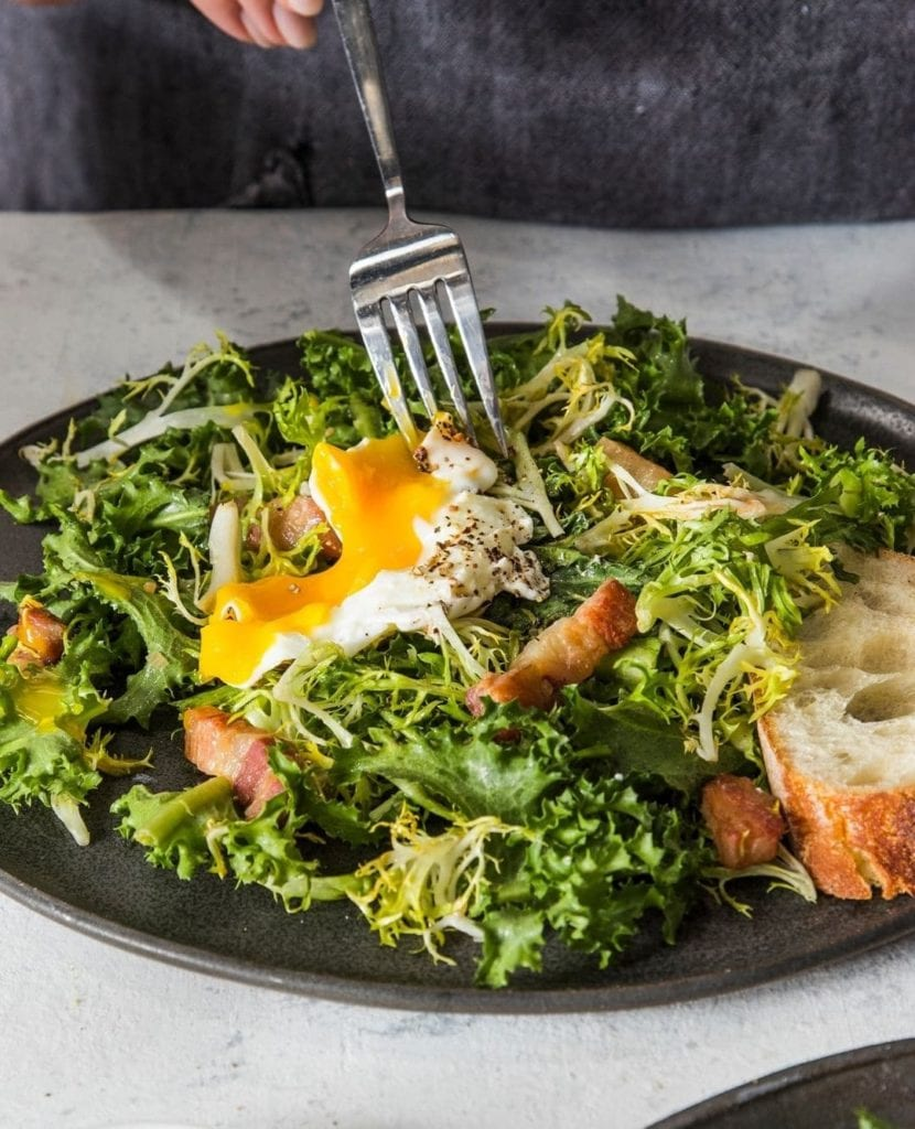 Fork breaking into the poached egg on top of a Lyonnaise salad, a traditional French food.