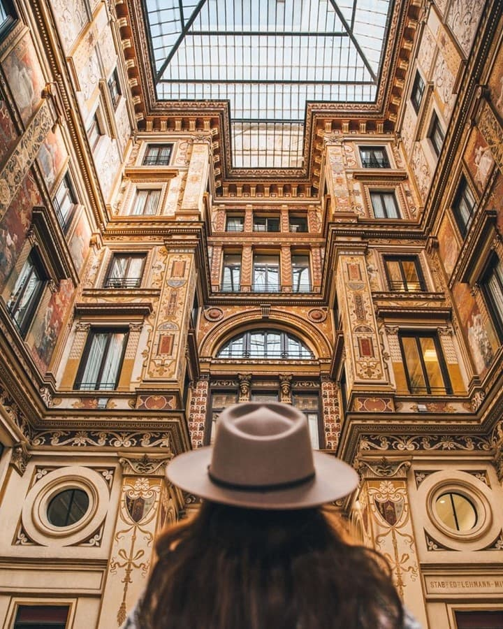Woman looking up in a galleria in Rome with a hat on, facing the ceiling.