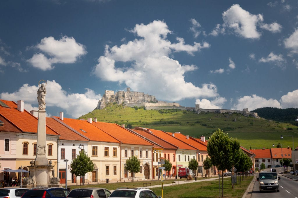 Spis Castle from town, a great item for the Slovakia bucket list.  Red roofs, castle ruins in background.