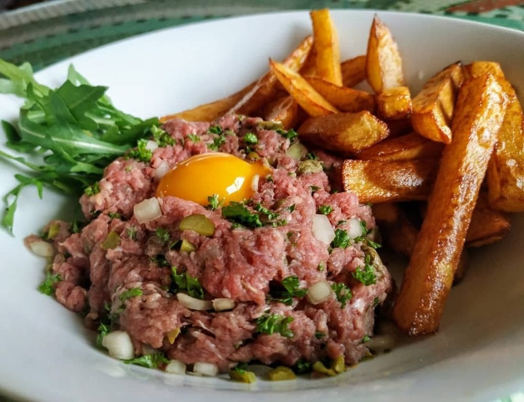 Minced raw beef mixed with onions and topped with raw egg yolk, plaed with french fries - one of the most traditional French dishes to try.