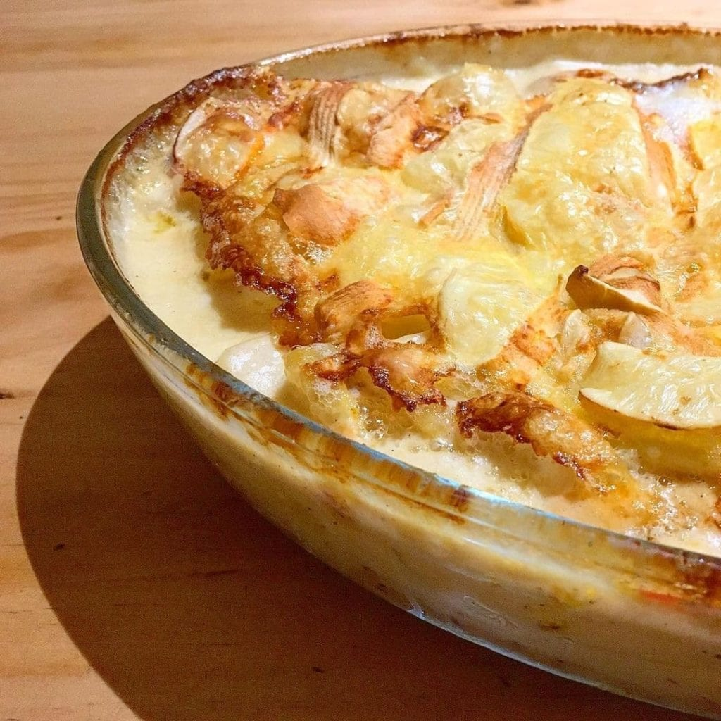 Half of a baking dish filled with tartiflette shown on a wooden table, a traditional French (Alsatian) food.