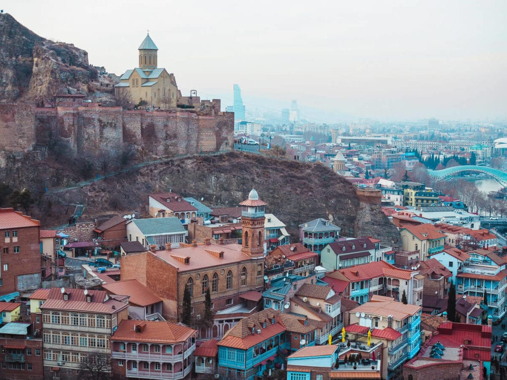 Red buildings along a mountainside in Tbilisi, Georgia, one of the best cities for digital nomads.