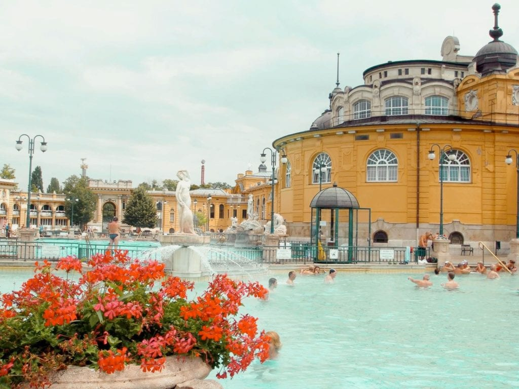 Outdoor thermal pools in Budapest, a relaxing way to spend a day in the turquoise pool surrounded by yellow buildings and red flowers.