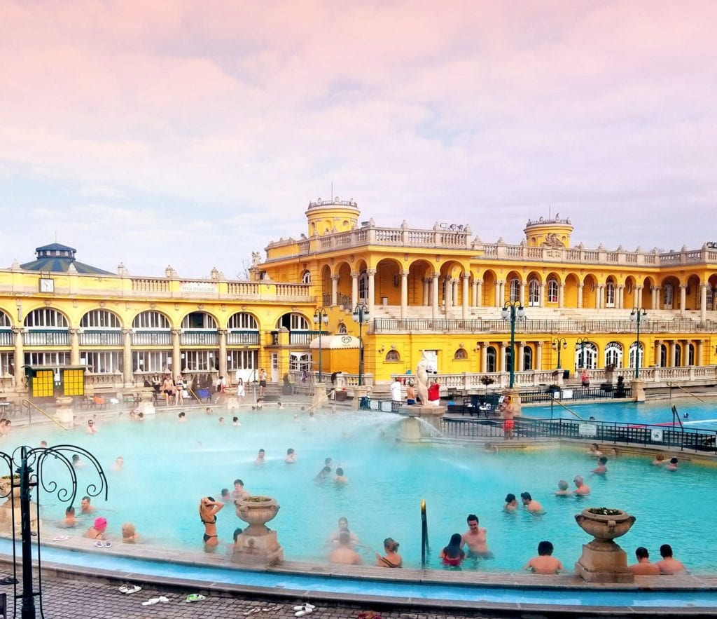 Outdoor pool at Szechenyi Thermal Spa in Budapest.  The water is light blue with steam rising off the surface with cotton candy pink and purple clouds in the sky.