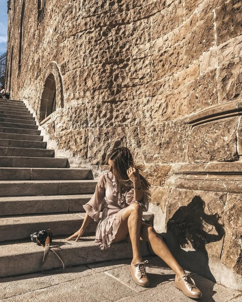 Woman sitting on the steps of Tibidabo, facing away from the camera in neutral shades, one of the most beautiful places in Barcelona.