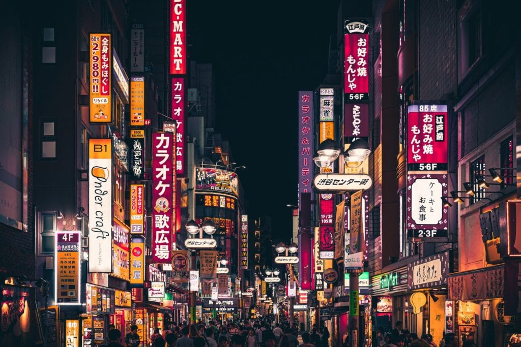 Purple and golden neon signs and marquis lit up down a street in Tokyo.