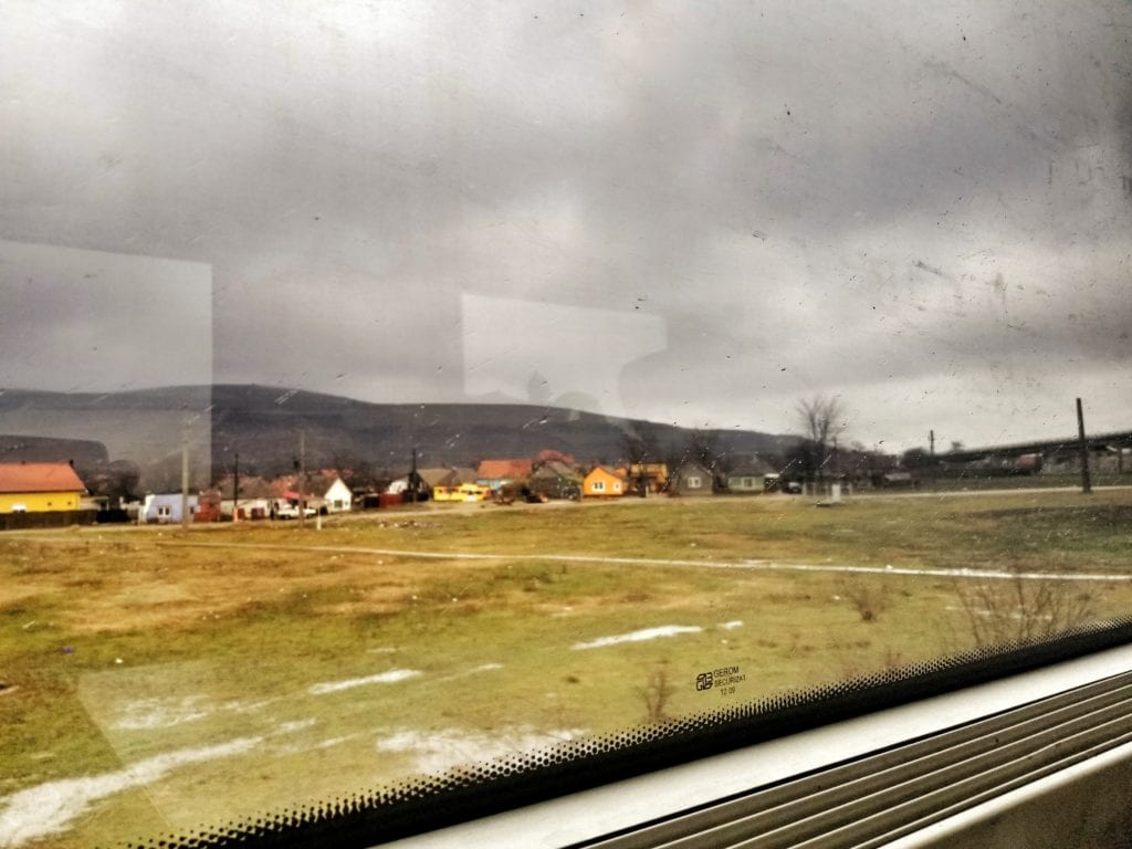 Rainy weather outside the train window looking at Romanian village.