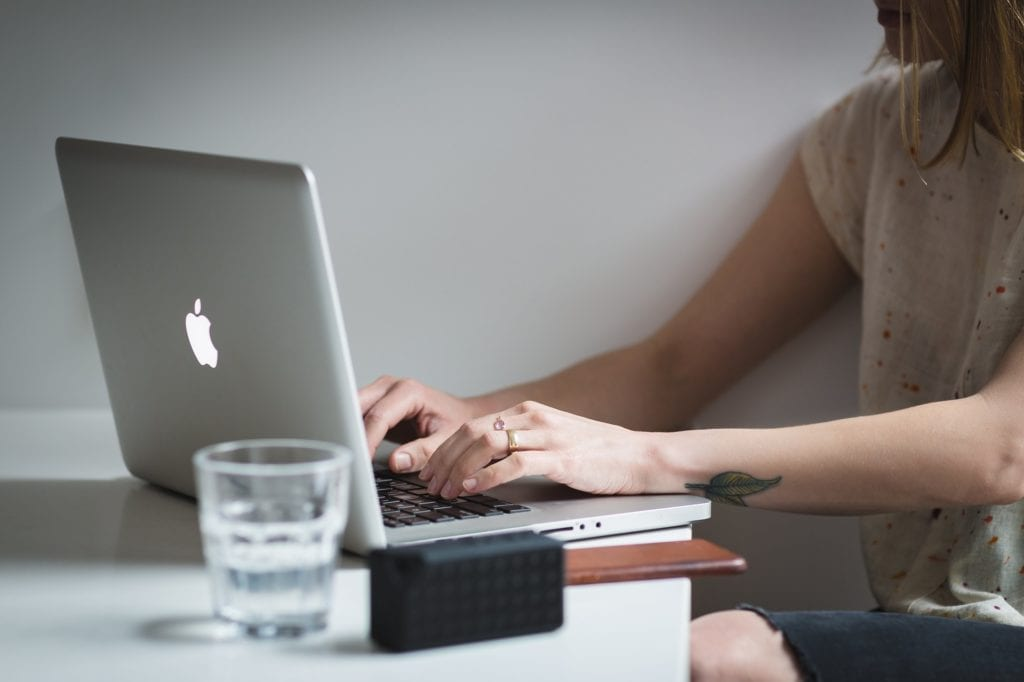 Woman typing on macbook working as a digital nomad.