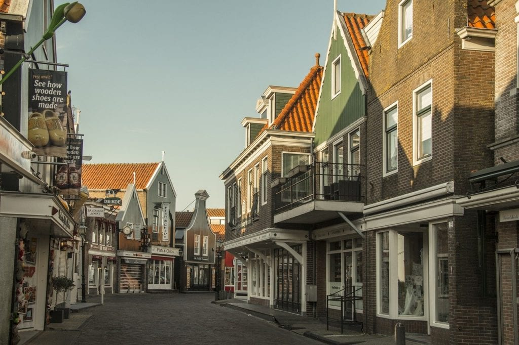Winding street in Volendam, Netherlands.  The buildings are reflected in sunlight and the street is empty.  Volendam is one of the best cities to visit in the Netherlands.