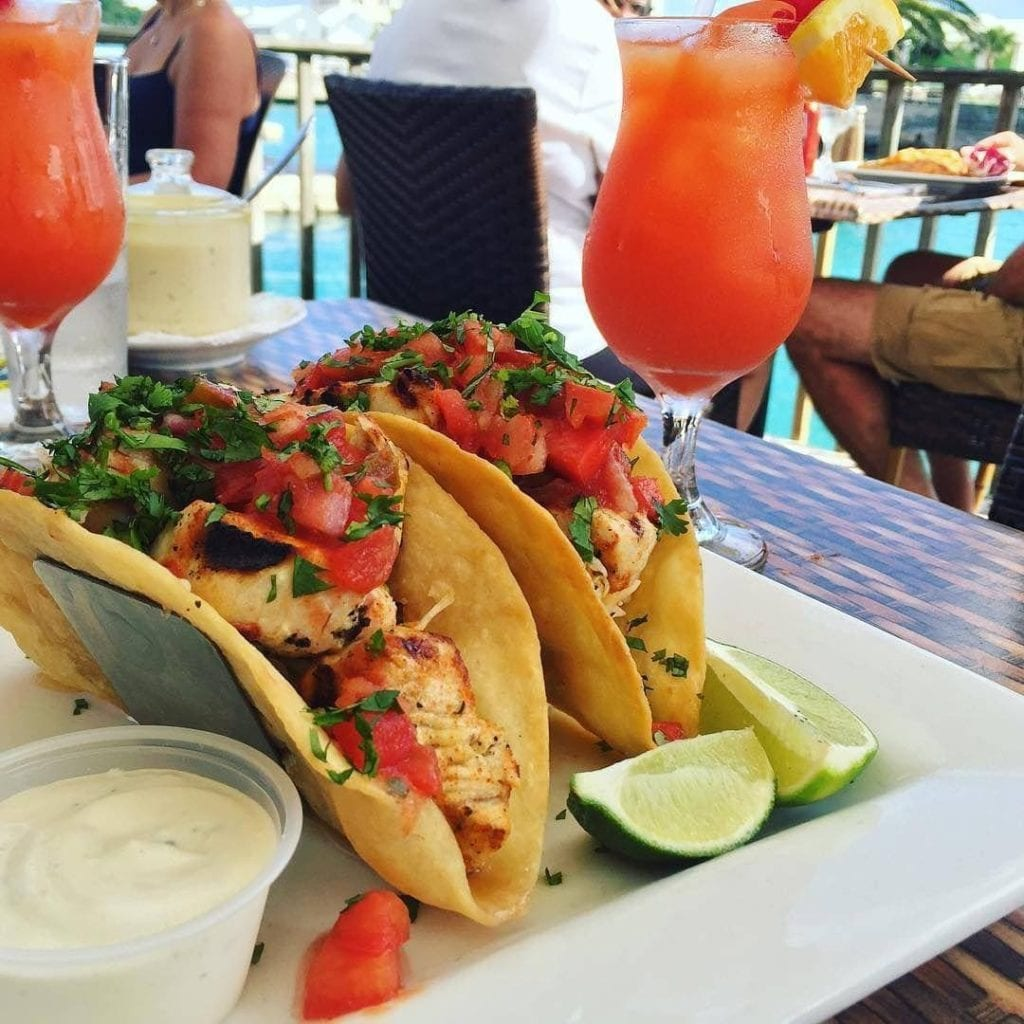 Wahoo Tacos from Wahoo's Bistro in Bermuda with two tall rum swizzles in the background