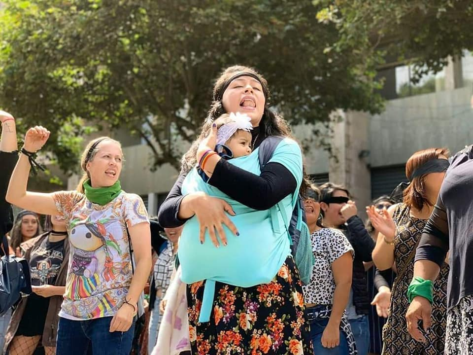 Woman in protest holding a baby in a bjorn close to her heart