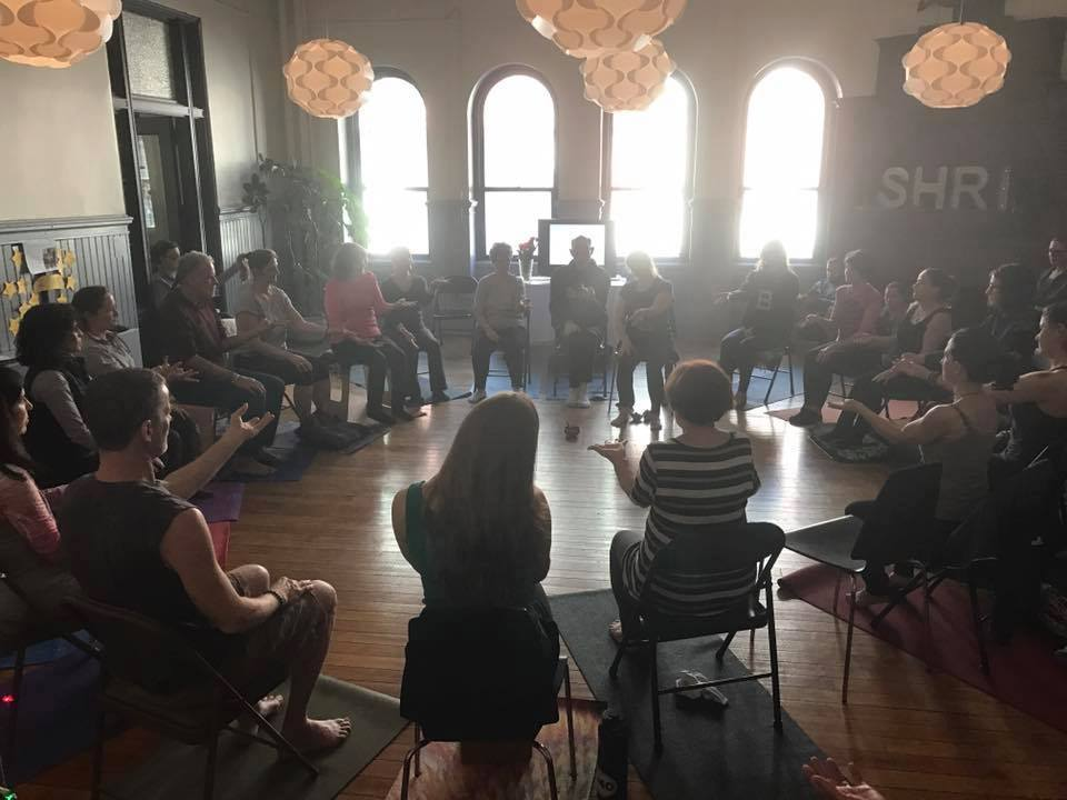 Yoga teacher trainees in a circle seated in chairs with large bulb lights and glare through windows.