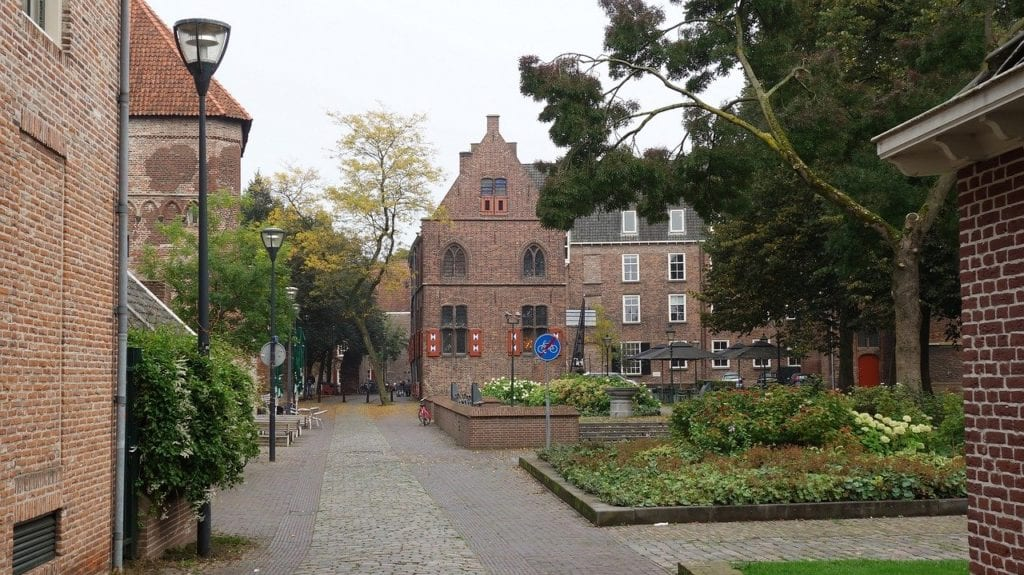 Monument and courtyard in Zwolle, Netherlands with squares of green plants in a courtyard and many trees.
