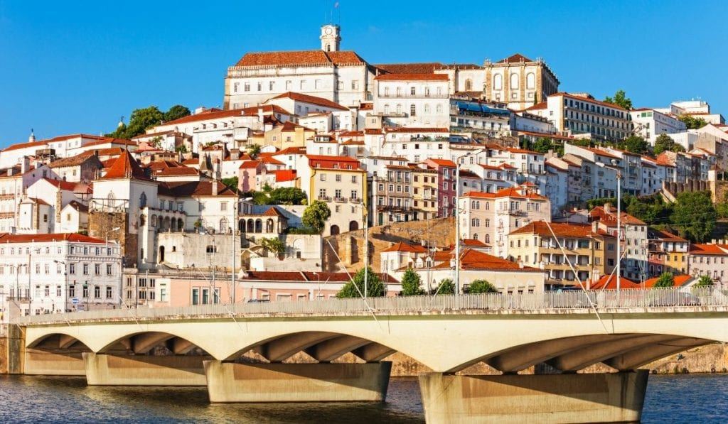 Riverfront Portuguese city, Coimbra, seen from the river with bridge in view.
