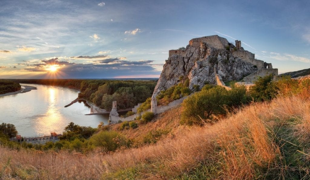 Devin Castle in Slovakia during golden hour with the sun setting over the Danube River. An easy day trip from Bratislava!