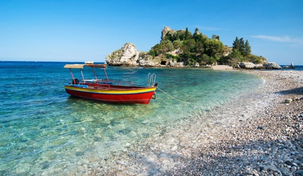 Lone red boat floating on the crystal turquoise waters of Isola Bella in Sicily with  island-like peninsula jutting into the water.