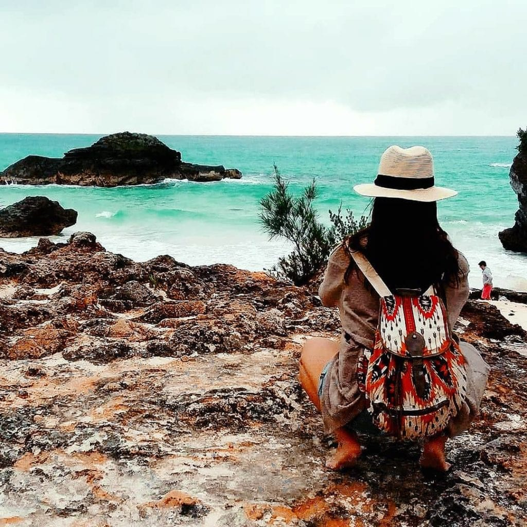 Woman crouched down on rocks in Bermuda taking a photo of Horseshoe Bay Beach.