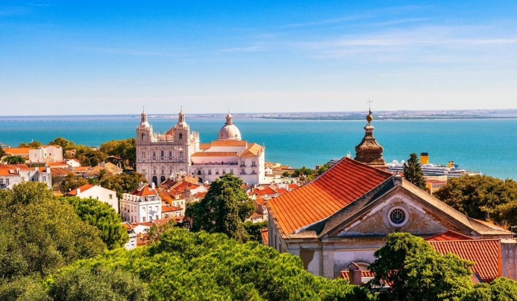 Sunny Lisbon, next to the ocean with red roofs and green trees in the foreground.