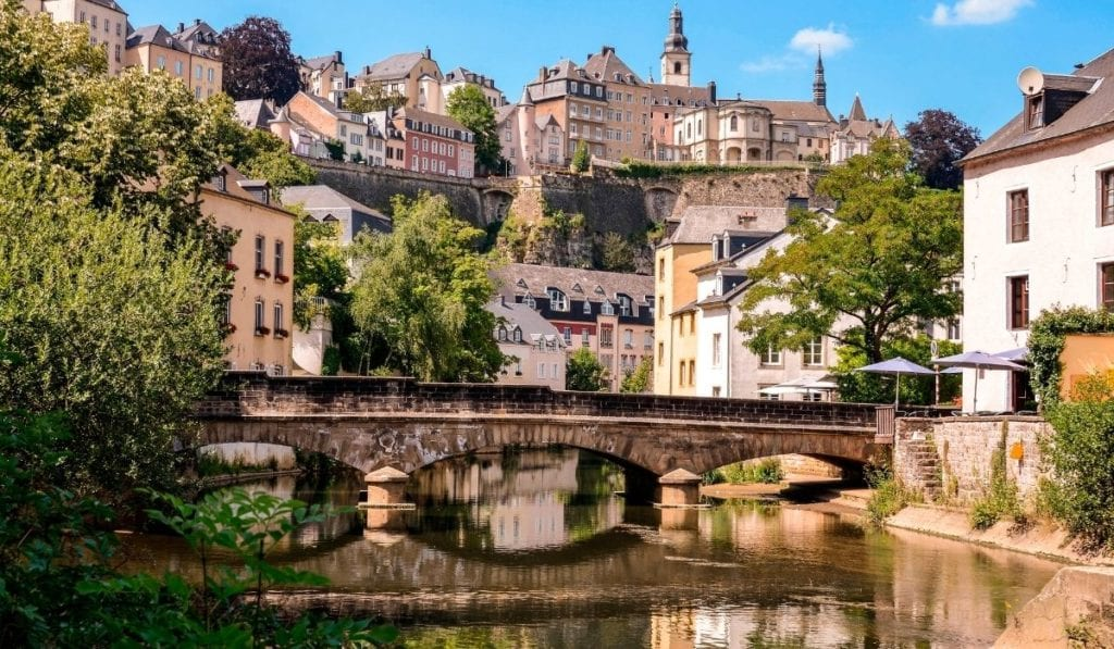 Luxembourg City, with old bidge over small river and buildings high on the hills.