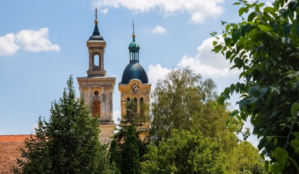 Two tall spires poking out through the trees in Modra, Slovakia, an easy day trip from Bratislava.