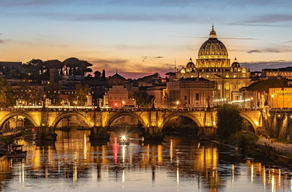 Ponte Umberto I during sunset with the lights of Rome reflecting over the Tiber river.