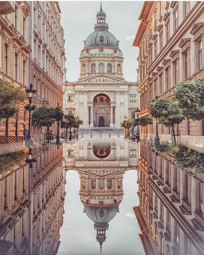 St. Stephen's Cathedral in Budapest seen reflected in a huge puddle in front of the beautiful building.