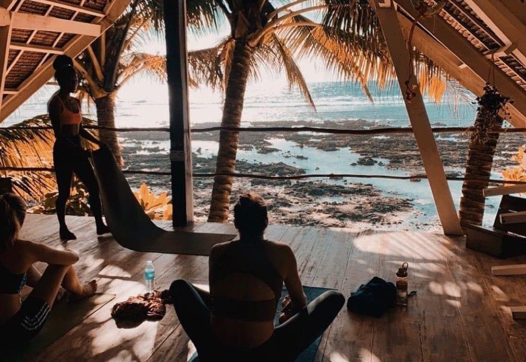 People on a beachside platform preparing for meditation or yoga with yoga mats.