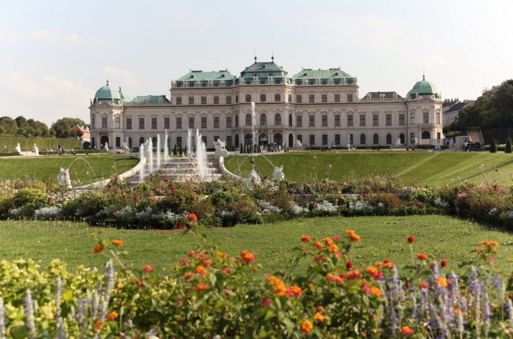 Belvedere Palace in Vienna with colorful flowers in the foreground in front of the fountain, one of the most famous landmarks in Austria.