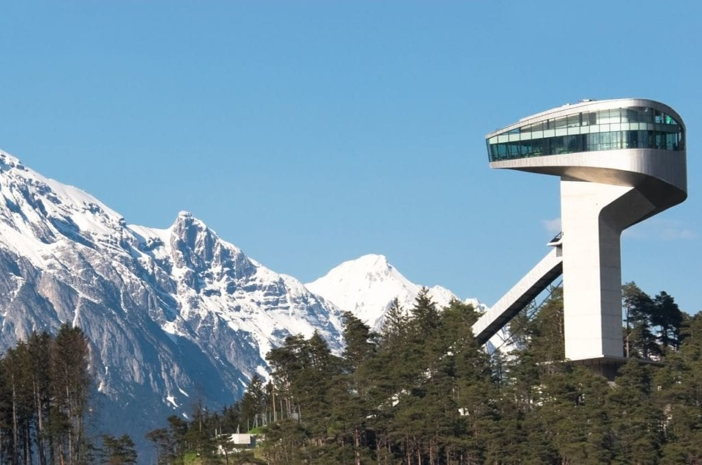 Bergisel ski jump in Innsbruck, Austria with the snow-covered Alps in the background.