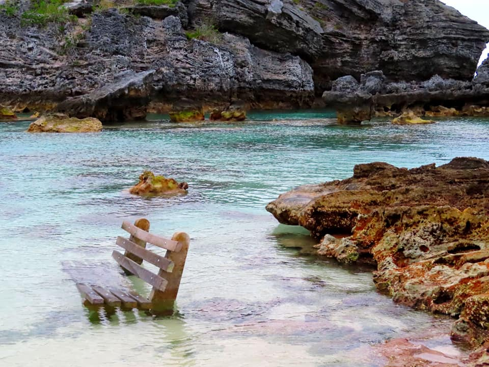 Semi-submerged bench in Tobacco Bay, Bermuda with water washing over it.