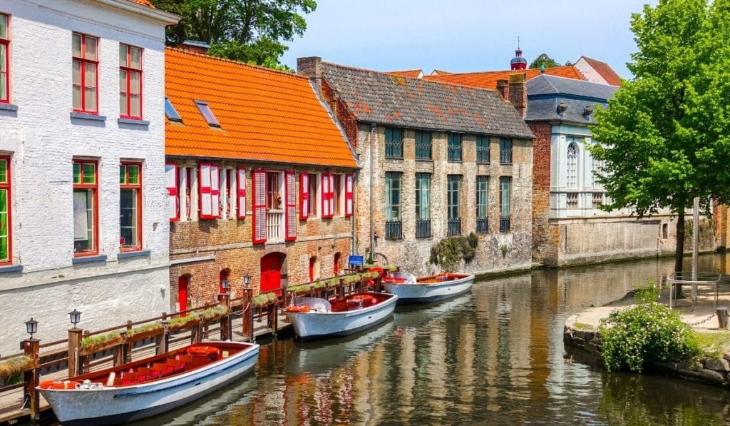 Boats lining a canal in Bruges, Belgium, a quaint day trip from Paris.