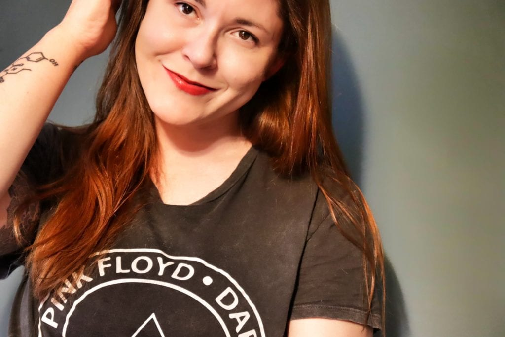 Woman modeling Pink Floyd t-shirt with solid background.