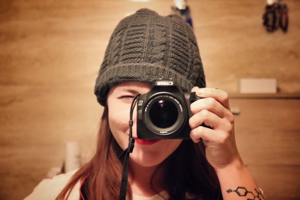Woman taking selfie with Canon camera.  Cameras are absolutely long-term travel essentials.