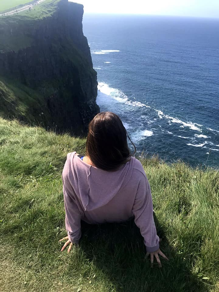 Woman sitting on the edge of the Cliffs of Moher facing the ocean.