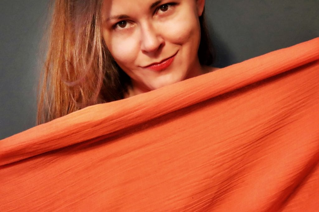 Woman smiling and holding up a scarf, long term travel essential that has multiple functions.