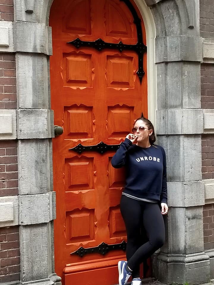 Woman smoking a joint outside a door in Amsterdam