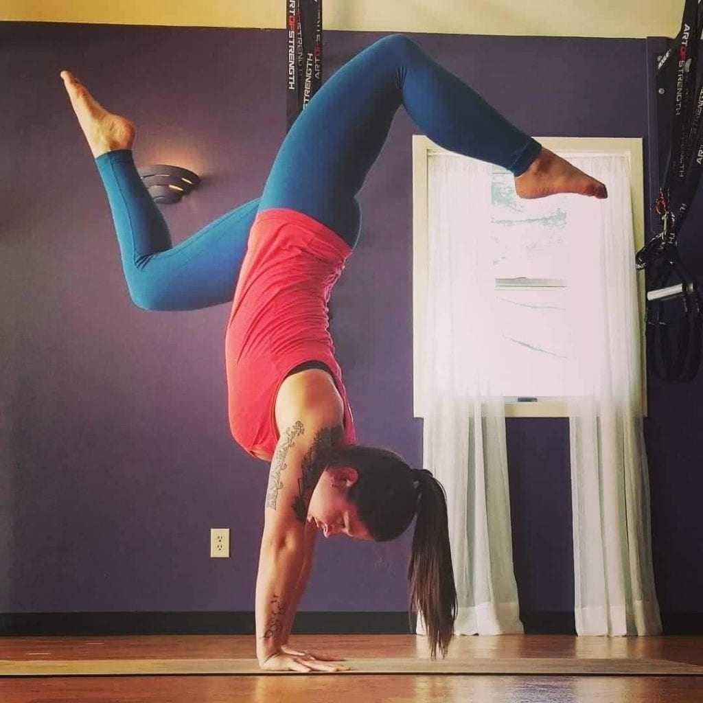 Woman doing stag handstand in a purple room with profile view.