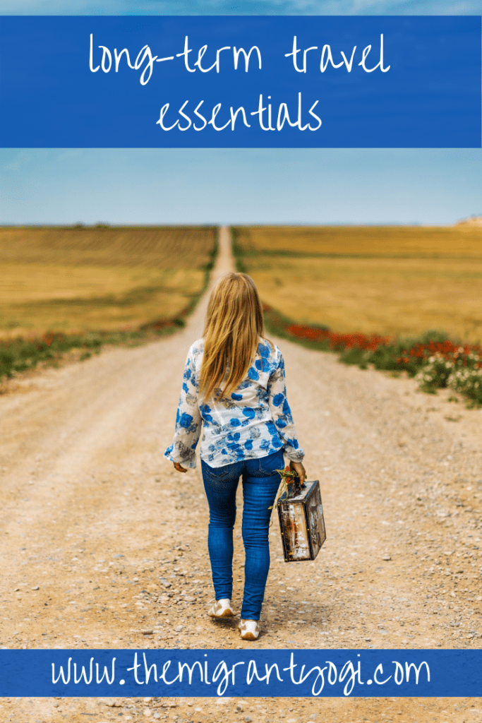 """Pinterest graphic with woman walking away down a long, dirt road with small handheld suitcase.  Text reads """"long term travel essentials""""."""