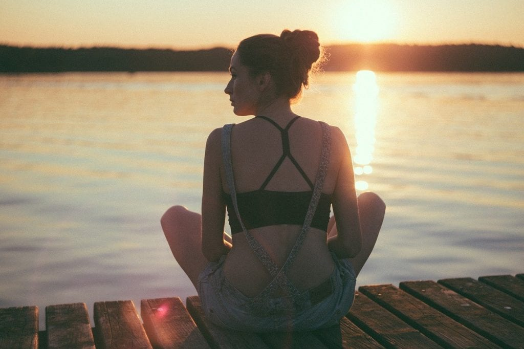 Woman sitting peacefully on a dock by a lake.
