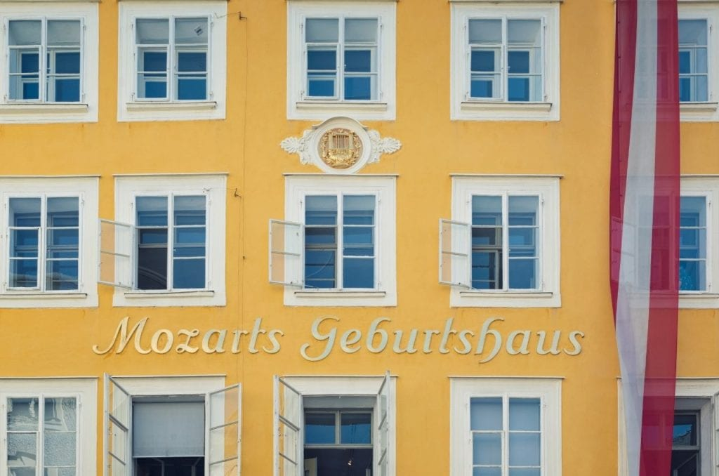 Outer facade of Mozart's house in buttercup yellow with a red and white long flag hanging in Salzburg.