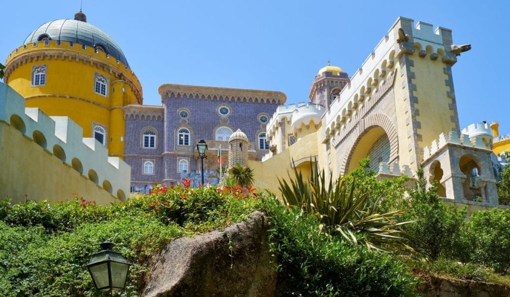 Colorful lilac and yellow buildings and a bright garden at Pena Palace in Sintra, Portual, an easy day trip from Porto.