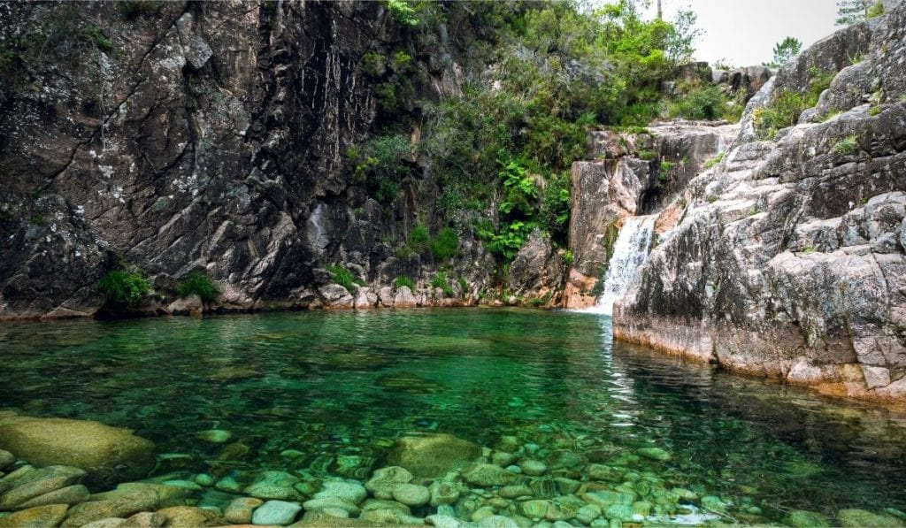 Hidden waterfall and lagoon in Peneda-Geres National Park, a great day trip from Porto.